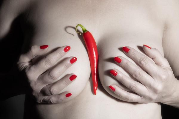 Rote Peperoni und Fingernägel auf nacktem Frauenoberkörper Sättigung reduziert